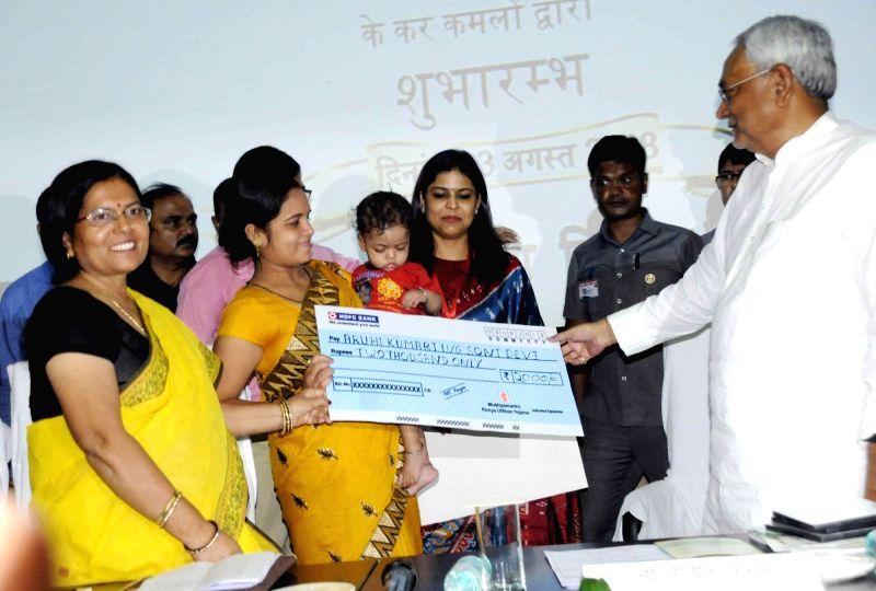 "Bihar Chief Minister Nitish Kumar hands over a cheque of Rs 2,000 to beneficiaries of ""Mukhyamantri Kanya Utthan Yojana"", in Patna, on  Aug 3, 2018 - Nitish Kumar"