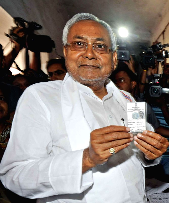 Bihar Chief Minister Nitish Kumar shows his voter's identity card at a polling booth during the fifth phase of 2014 Lok Sabha Polls in Patna on April 17, 2014.