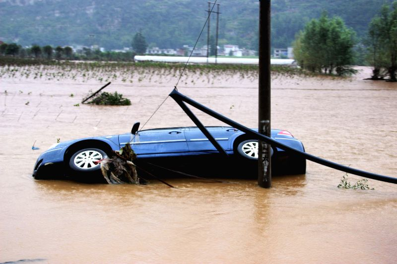 Photo taken on Aug. 12, 2014 shows a car in flood waters in Houchang Township of Weining County, southwest China's Guizhou Province. The death toll from continuous ...