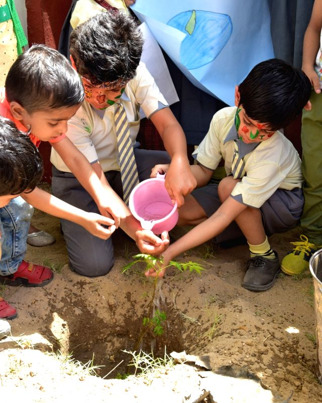"Bikaner: School students plant a sapling on ""World Earth Day"" in Bikaner on April 22, 2017."