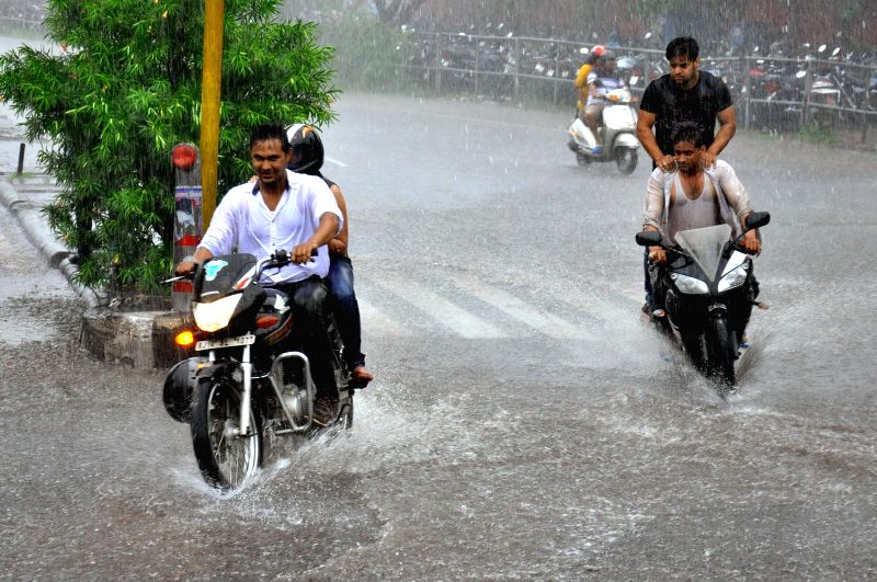 Bikers enjoy themselves as they ride on waterlogged streets of Jaipur during rains on Aug 3, 2014.
