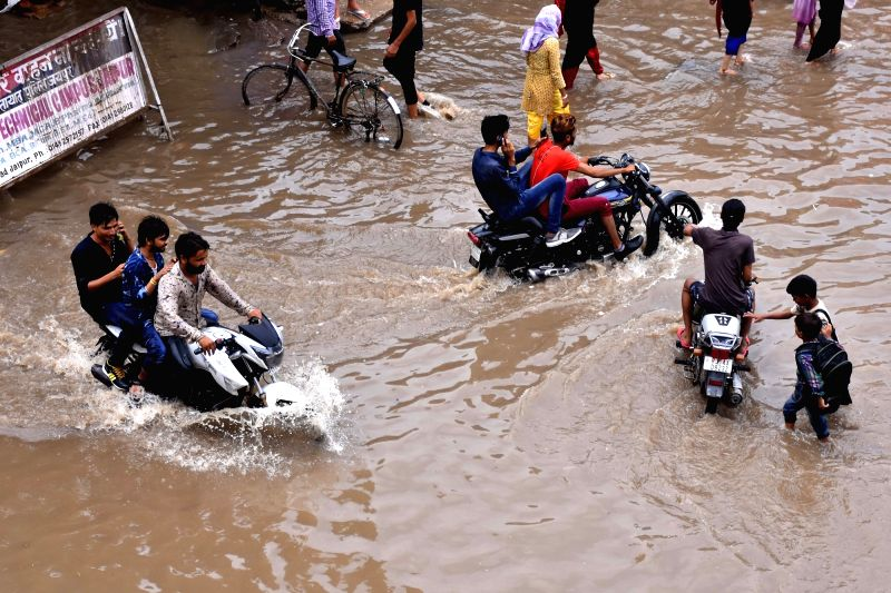 Bikers struggle through water-logged streets of Sanganer, Rajasthan on July 22, 2018.