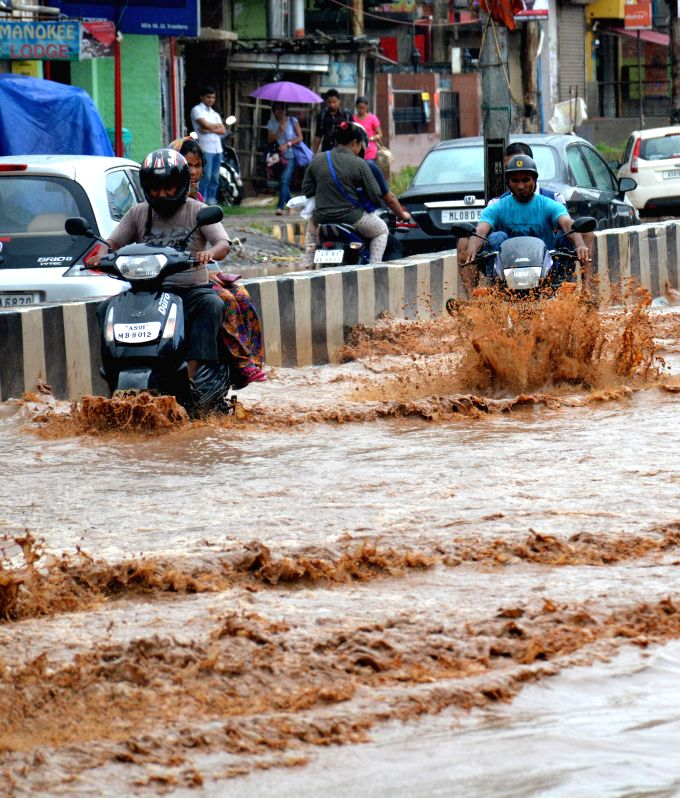Bikers struggle through waterlogged streets of Guwahati after heavy rains on Aug 3, 2014.