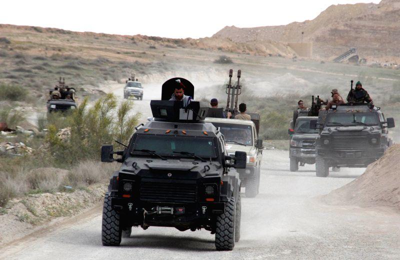 BIR AL-Some Libya Dawn fighters go into the combat zone on their armed vehicles near Bir al-Ghanam, Libya, on March 21, 2015. Clashes continued between Libya Dawn ...