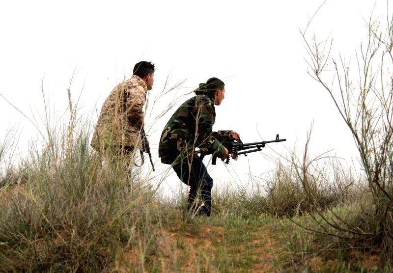 BIR AL-Two Libya Dawn fighters identify positions of their rivals near Bir al-Ghanam, Libya, on March 21, 2015. Clashes continued between Libya Dawn fighters and ...