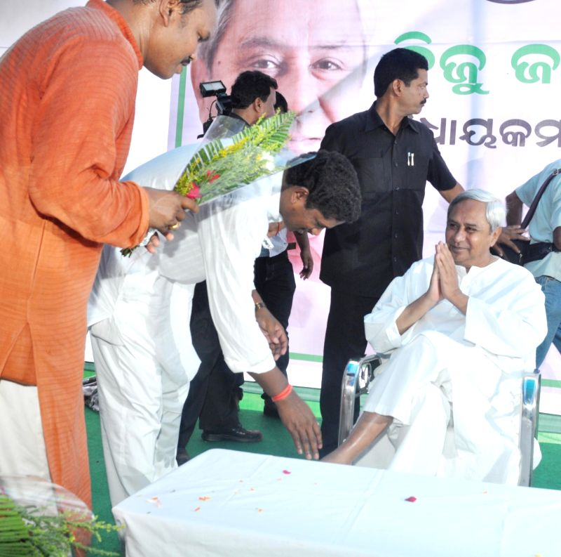 BJD leader Ramesh Majhi touches the feet of party chief and Odisha Chief Minister Naveen Patnaik during a prgramme after party's outstanding performance in Assembly as well as 2014 Lok Sabha Polls in