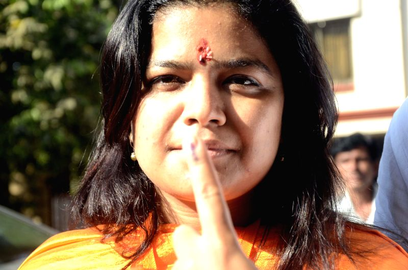 BJP candidate for upcoming 2014 General Election from North Mumbai, Poonam Mahajan shows her fore fingers marked with phosphorous ink after casting her vote at a polling booth during the sixth phase .