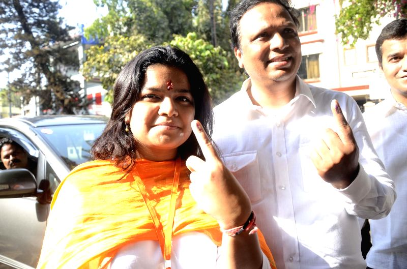 BJP candidate for upcoming 2014 General Election from North Mumbai, Poonam Mahajan and party's Mumbai unit chief Ashish Shelar show their fore fingers marked with phosphorous ink after casting their .