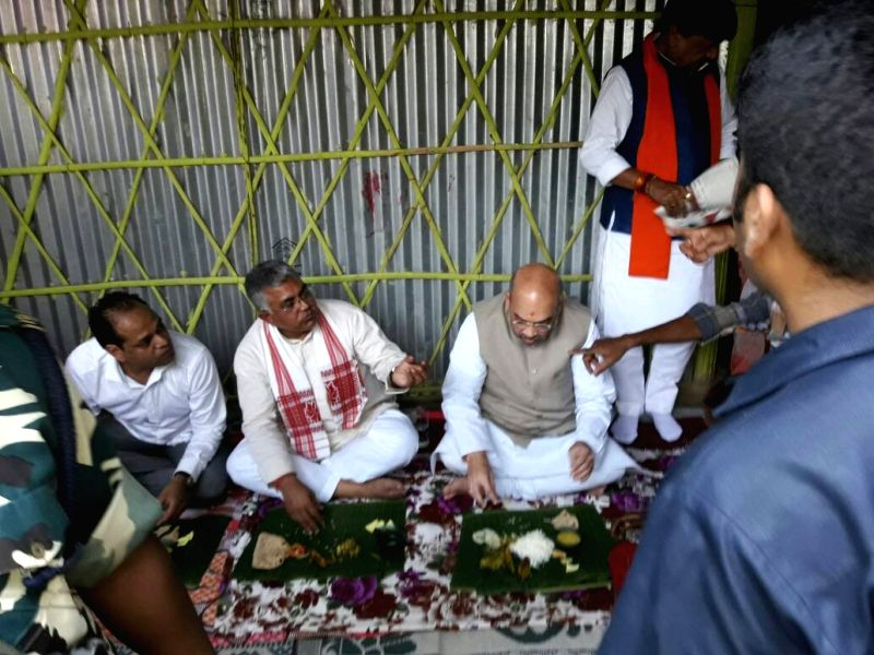 BJP chief Amit Shah and West Bengal party chief Dilip Ghosh have food sitting on ground during their visit to Kotiyajote in Naxalbari near Siliguri on April 25, 2017. - Amit Shah and Dilip Ghosh