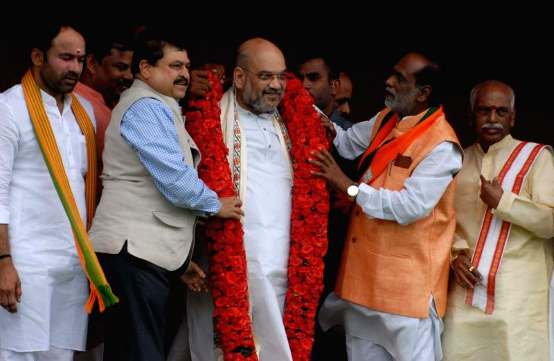 BJP chief Amit Shah being felicitated by Telangana BJP chief K Laxman on his arrival in Hyderabad on July 13, 2018. Also seen party leaders G Kishan Reddy and Bandaru Dattatreya. - Amit Shah and G Kishan Reddy