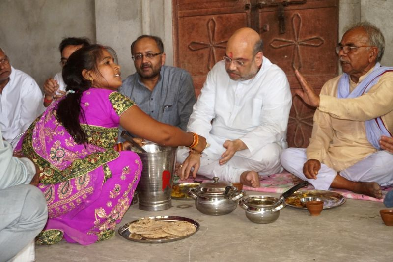 BJP chief Amit Shah haves lunch with a Dalit family in Jogiyapur near Varanasi on May 31, 2016. Also seen party leader Siddharth Nath Singh. - Amit Shah and Siddharth Nath Singh