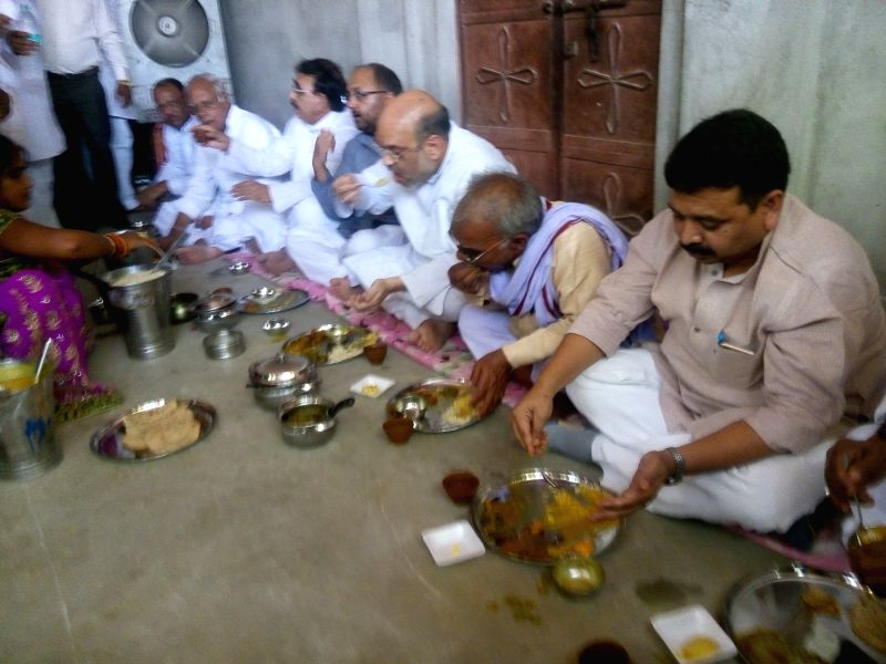 BJP chief Amit Shah haves lunch with a Dalit family in Jogiyapur near Varanasi on May 31, 2016. - Amit Shah
