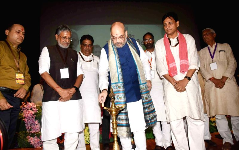 BJP chief Amit Shah lights the lamp to inaugurate a party meeting, in Patna on July 12, 2018. Also seen Bihar Deputy Chief Minister and BJP leader Sushil Kumar Modi and BJP state president ... - Amit Shah, Sushil Kumar Modi and Nityanand Rai