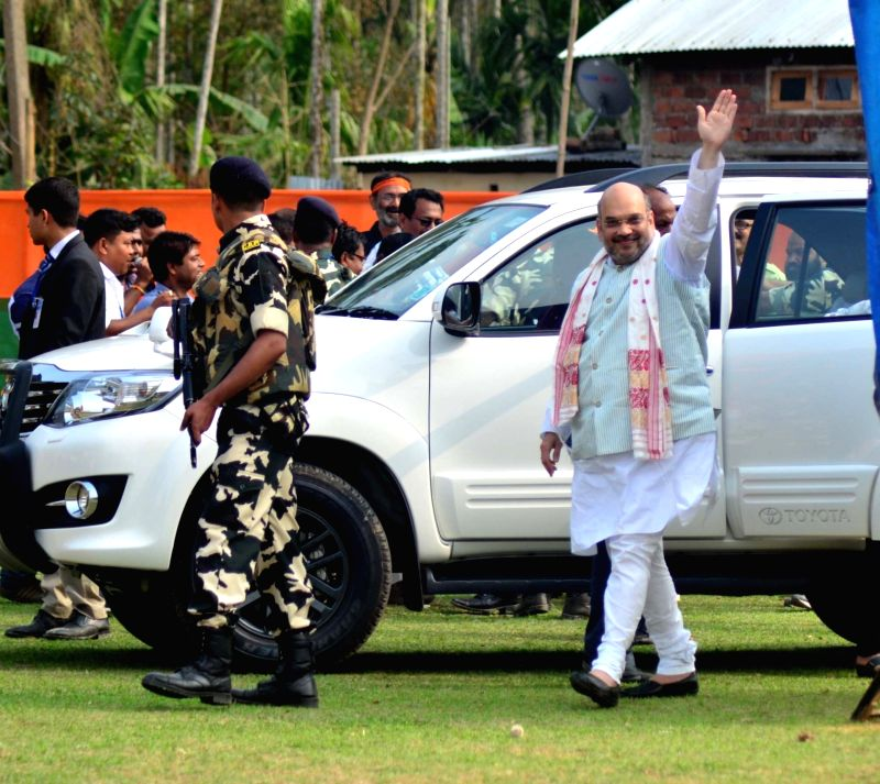 BJP chief Amit Shah waves to the public as he arrives to address a rally in Kamrup district of Assam ahead of the second phase of state assembly elections on April 5, 2016. - Amit Shah