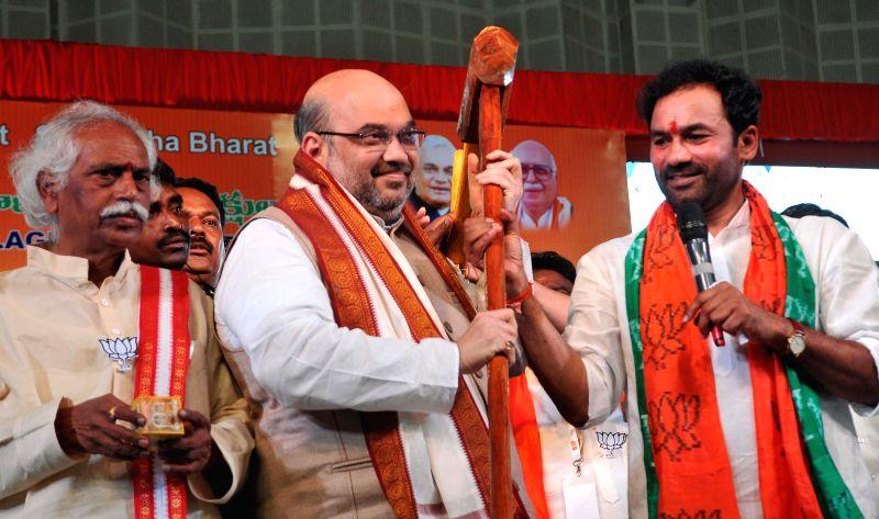 BJP chief Amit Shah with BJP leader Bandaru Dattatreya and Telangana BJP chief G. Kishan Reddy during a programme in Saroornagar Indoor Stadium in Hyderabad on Aug 22, 2014. - G. Kishan Reddy