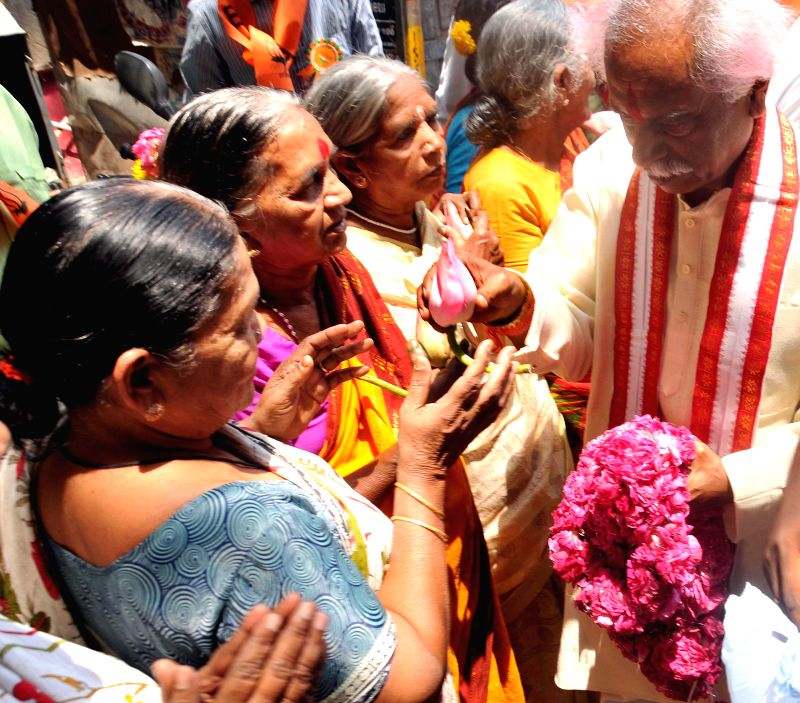 BJP leader Bandaru Dattatreya distributes lotuses among the people during an election campaign at Narayanguda in Hyderabad on April 13, 2014.
