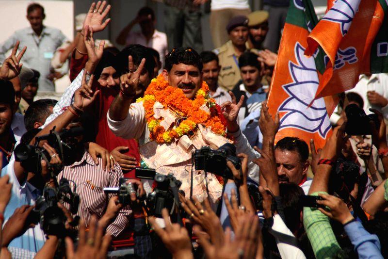 BJP leader Jugal Kishore Sharma celebrates after winning Jammu Lok Sabha Seat in Jammu on May 16, 2014.