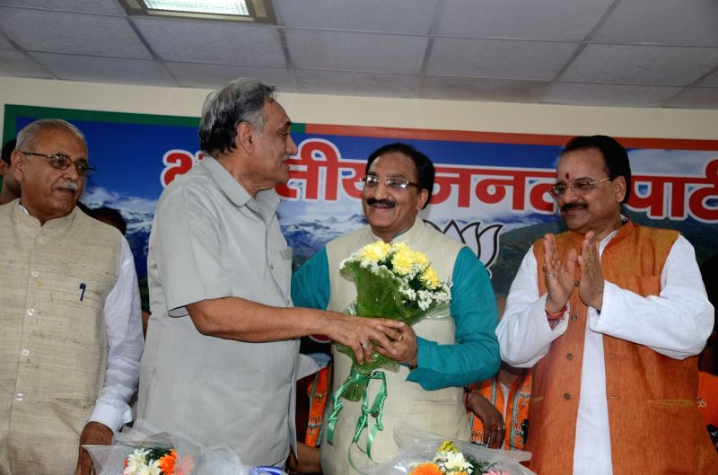 BJP leader Ramesh Pokhriyal Nishank greets rebel Congress leader Vijay Bahuguna who along with other rebel leaders have joined the party in Dehradun, on May 22, 2016.