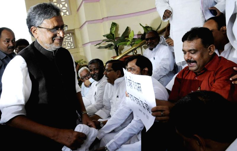 BJP leader Sushil Kumar Modi arrives at Bihar Legislative Council amidst demonstration by JD (U) legislators in Patna on July 8, 2014. - Sushil Kumar Modi