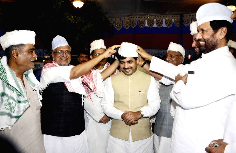 BJP leaders Sushil Kumar Modi, Syed Shahnawaz Hussain and LJP chief and Union Minister for Consumer Affairs, Food and Public Distribution Ramvilas Paswan during an iftar party hosted by Paswan in ... - Sushil Kumar Modi