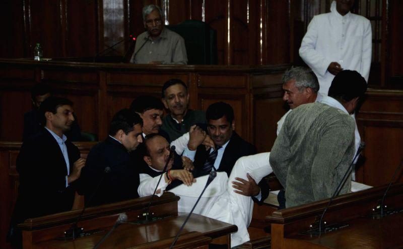 BJP legislator and Leader of Opposition Vijender Gupta forcibly marshalled out of the Delhi Assembly, in New Delhi on Nov 30, 2015. - Vijender Gupta