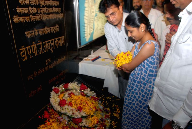 BJP MP Kirit Somaiya helps a handicapped girl as she pays tribute to those who died in `11/7 Mumbai train blasts` on its eighth anniversary at Mahim Railway Station in Mumbai on July 11, 2014.