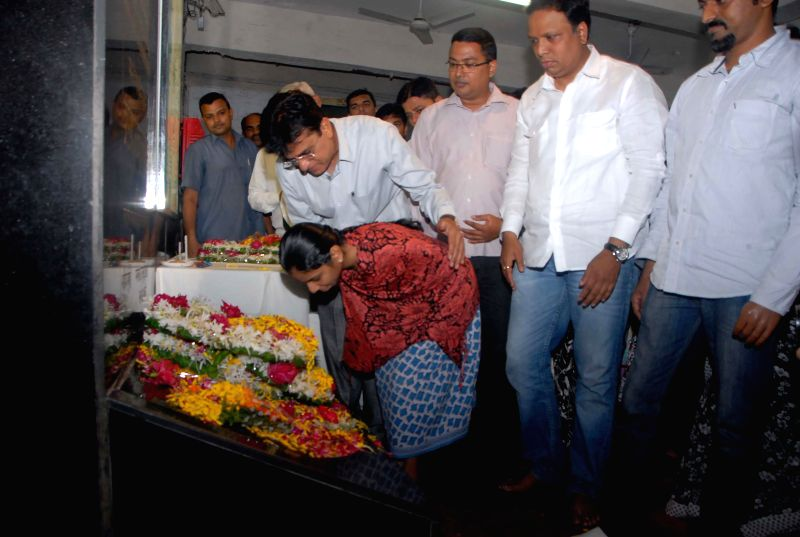 BJP MP Kirit Somaiya helps a handicapped woman as she pays tribute to those who died in `11/7 Mumbai train blasts` on its eighth anniversary at Mahim Railway Station in Mumbai on July 11, 2014.