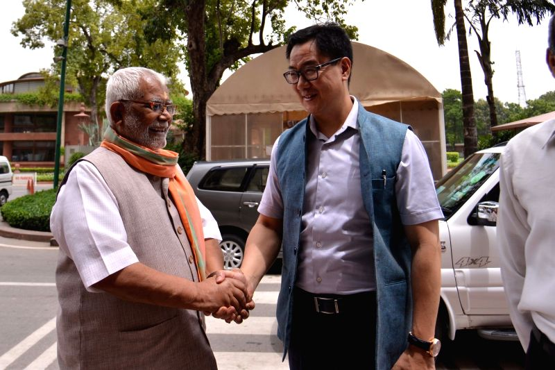BJP MPs Kiren Rijiju and Hukmdev Narayan Yadav greet each other as they arrive at Parliament, in New Delhi on Aug 2, 2018. - Hukmdev Narayan Yadav