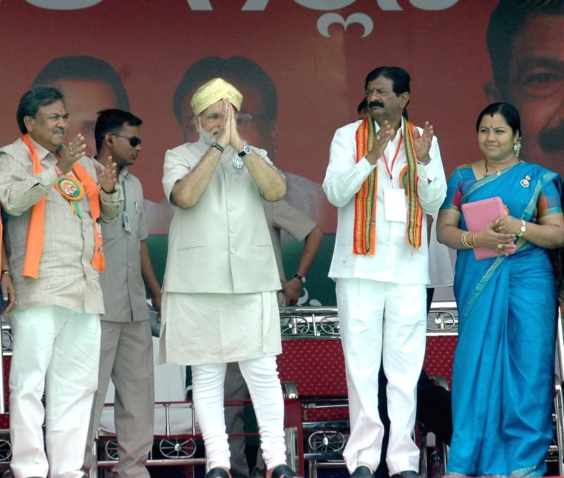 BJP Prime Ministerial candidate and Gujarat Chief Minister Narendra Modi  with party's candidate for 2014 Lok Sabha Election from Chikkaballapur,  B N Bache Gowda and others during a rally in ...