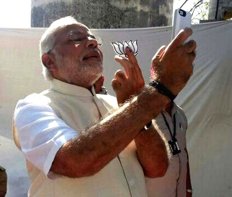 BJP Prime Ministerial candidate and Gujarat Chief Minister Narendra Modi  clicks a 'selfie' (a self-portrait photograph) after casting his vote at Ranip in Ahmedabad on April 30, 2014.