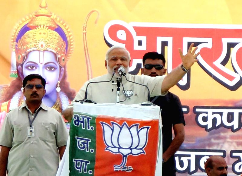 BJP Prime Ministerial candidate and Gujarat Chief Minister Narendra Modi addresses during a rally with a huge picture of lord Ram in the background, in Faizabad of Uttar Pradesh  on May 5, 2014.