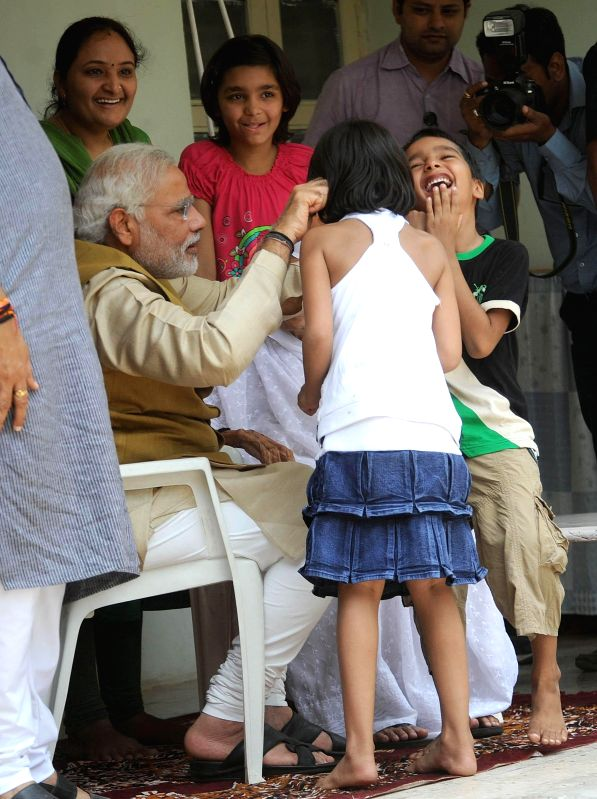 BJP Prime Ministerial candidate and Gujarat Chief Minister Narendra Modi with a child at his brother's residence in Gandhinagar on May 16, 2014.
