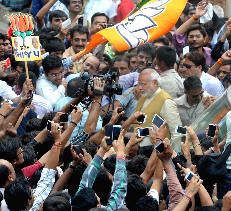 BJP Prime Ministerial candidate and Gujarat Chief Minister Narendra Modi surrounded by fans and the media in Gandhinagar on May 16, 2014.