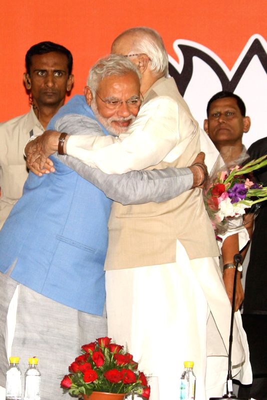 BJP Prime Ministerial candidate Narendra Modi hugs party veteran L K Advani during a press conference in New Delhi on May 17, 2014. - Narendra Modi and L K Advani