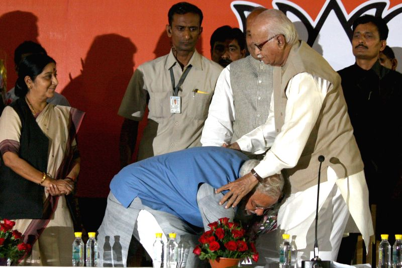 BJP Prime Ministerial candidate Narendra Modi touches the feet of party veteran L K Advani during a press conference in New Delhi on May 17, 2014. Party leader Sushma Swaraj also seen. - Narendra Modi, Sushma Swaraj and L K Advani