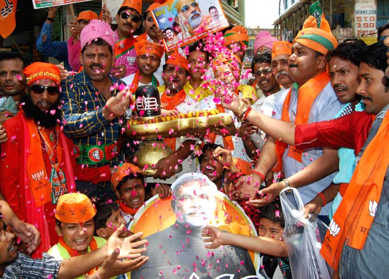 BJP supporters celebrate as counting for 2014 Lok Sabha Election is underway and the party is leading nationally, in Varanasi on May 16, 2014.