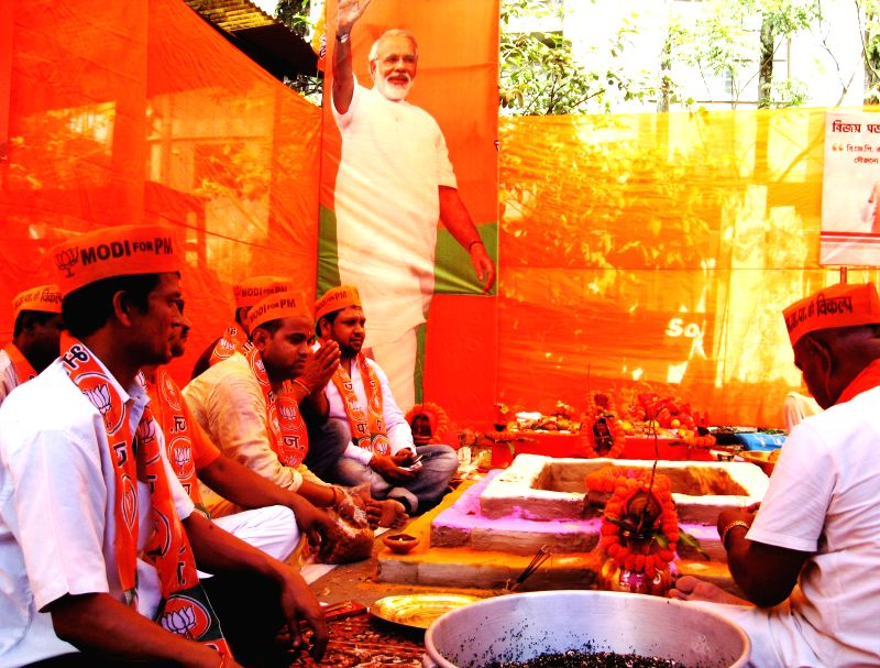 BJP supporters perform 'Yajna' for BJP Prime Ministerial candidate and Gujarat Chief Minister Narendra Modi's victory in 2014 Lok Sabha Election at Bagha Jatin Colony of Siliguri in West Bengal on ...