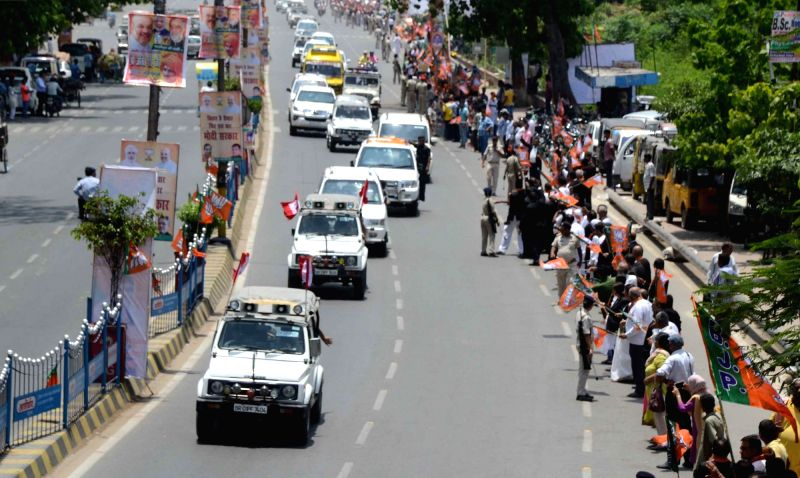 BJP supporters wave the party's flags as BJP chief Amit Shahs' convoy passes by a Patna road, on July 12, 2018.