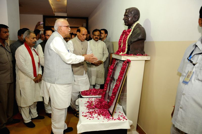 BJP veteran L K Advani pays tribute to BJP ideologue and Jana Sangh founder Shyama Prasad Mukherjee on his birth anniversary at party headquarters in New Delhi on July 6, 2014. Also seen Union Home .. - L K Advani, Shyama Prasad Mukherjee and Rajnath Singh
