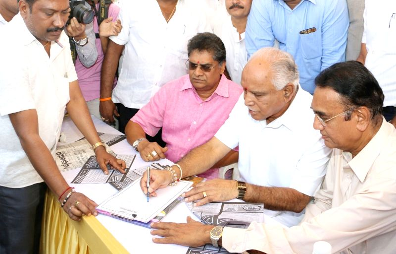 BJP vice-president BS Yeddyurappa collects signatures from people outside KSRTC during the launch of party`s Signature Campaign against Anti Corruption Bureau (ACB) in Bengaluru on April ...