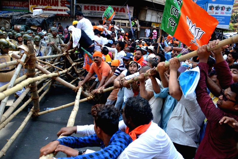 BJP workers break barricades during a protest against the law and order situation in West Bengal and fake cases lodged against their party workers among other issues in Lalbazar of Kolkata ...