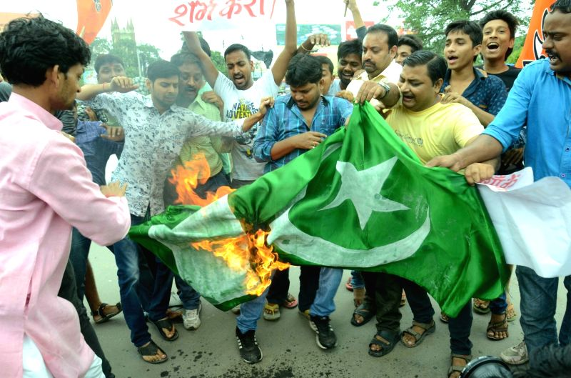 BJP workers burn Pakistan's national Flag during a protest against Pakistan for terror attacked in India; in Patan on July 19, 2016.