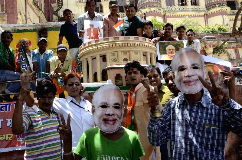 BJP workers celebrate as exit polls indicate party's victory in 2014 Lok Sabha Polls, in front of a replica of Parliament in Patna on May 15, 2014.