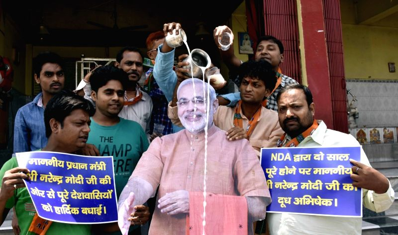 BJP workers give a milk bath to the cutout of Prime Minister Narendra Modi on completion of his two years in office in Patna on May 25, 2016. - Narendra Modi