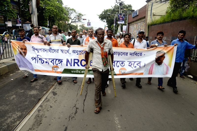 "BJP workers participate in a march to demand publication of a National Register of Citizens (NRC) in West Bengal to drive out ""infiltrators from Bangladesh"" in Kolkata on Aug 2, ..."