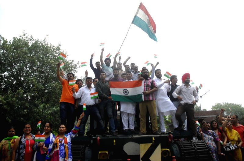 BJP workers stand on a Pakistani tank captured by Indian forces during 1965 Indo Pak, while paying tribute to the soldiers who sacrificed their lives in Kargil war on the occasion of Kargil ...