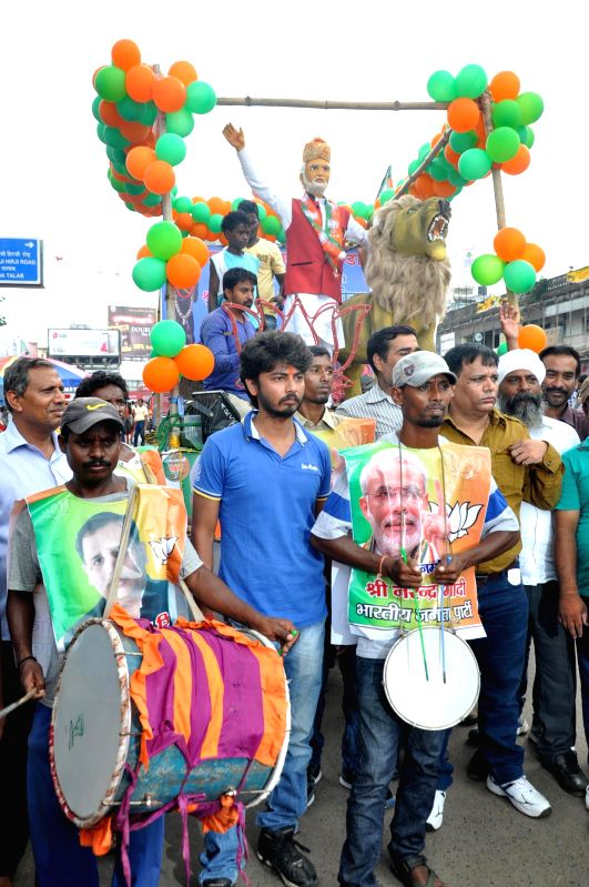 BJP workers take out a procession with a replica of Prime Minister Narendra Modi on the eve of his visit to Ranchi on Aug 20, 2014. - Narendra Modi