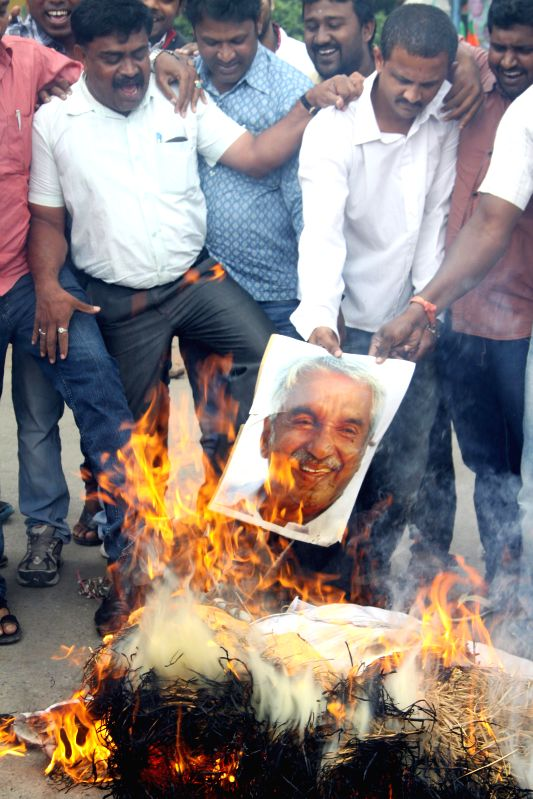 BJP Yuva Morcha activists burn effigies of Kerala Chief Minister Oommen Chandy during a demonstration in Bangalore on July 30, 2014. - Oommen Chandy