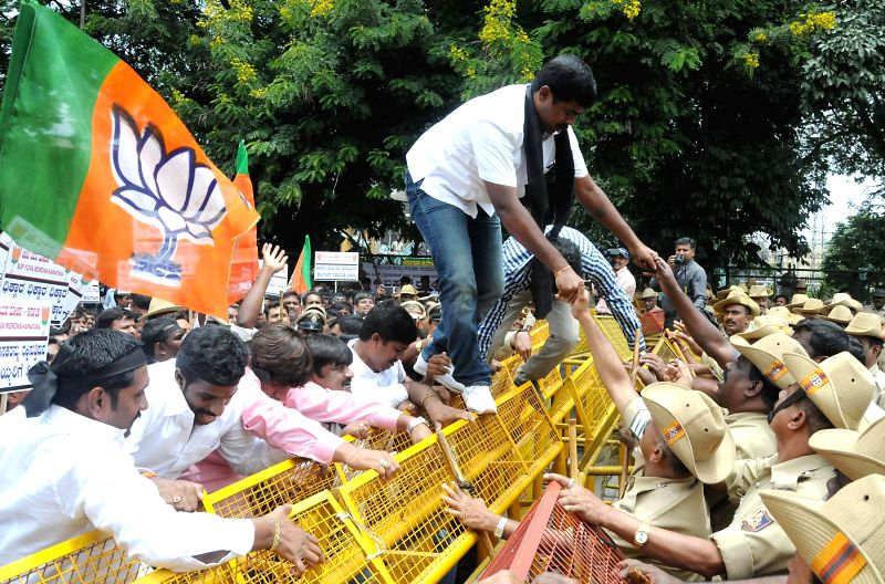 BJP Yuva Morcha activists jump barricades during a demonstration against alleged rape of a 6-year-old student in Bangalore on July 21, 2014.