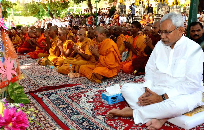 Para umat termasuk para bhikkhu dan Ketua Menteri negara bagian Bihar, Nitish Kumar (kanan), menghadiri puja bakti di bawah pohon Bodhi.